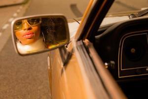 retrò anni '70 donna moda afro con occhiali da sole guardandosi allo specchio.