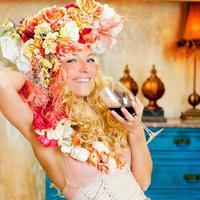 womand bionda moda barocca che beve vino rosso