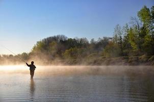 silhouette di pescatore a mosca in nova scotia foto