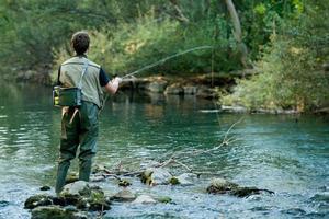 pescatore che pesca su un fiume foto