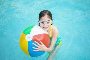 ragazza carina che gioca con il pallone da spiaggia in piscina foto