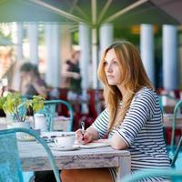 donna che beve caffè e scrivere note nella caffetteria foto