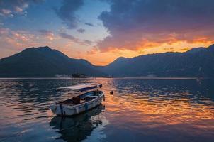 piccola barca galleggia ormeggiata nella baia di kotor al crepuscolo, montenegro