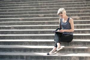 giovane donna bionda utilizzando tablet.