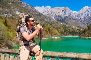 escursionista che cattura foto in riva al lago