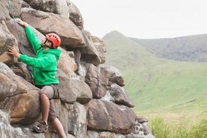 uomo concentrato che scala una grande parete rocciosa