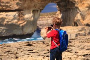 ragazzino che fa foto della finestra azzurra sull'isola di gozo