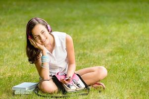 ragazza dell'allievo con le cuffie che si siedono sull'erba