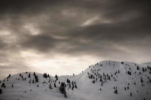 montagne innevate con cielo drammatico