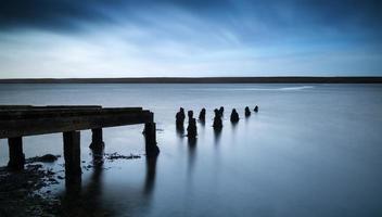 lunga esposizione paesaggio del vecchio molo abbandonato che si estende nel lago