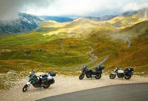 paesaggio con strada di montagna e tre motociclette