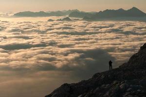 alpinista sta osservando il cielo nuvoloso di mattina foto