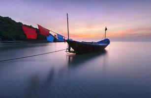 barche in spiaggia durante la luce del tramonto vista sul mare in Thailandia.
