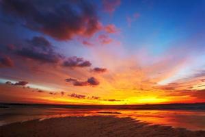 un caldo tramonto arancione in un cielo blu che si oscura foto