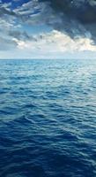 nuvoloso cielo blu sopra una superficie blu del mare