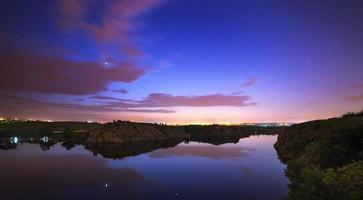 bel cielo notturno al fiume con stelle e nuvole foto
