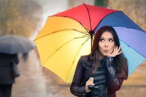 sorpreso autunno donna con ombrello arcobaleno