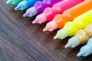 vernice colorata - bottiglie con pigmenti colorati su fondo in legno