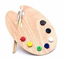 tavolozza di arte in legno con vernice e pennelli isolati su bianco foto