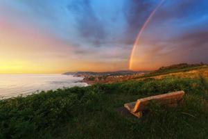 panchina vicino alla costa di sopelana con arcobaleno foto