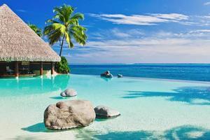 una piscina a sfioro con spiaggia artificiale e oceano blu