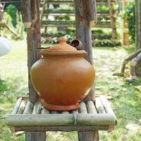 vaso di argilla tailandese per acqua potabile e mestolo di cocco