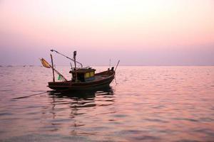 barca da pesca al tramonto foto