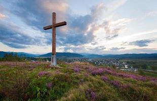vista paese sera d'estate con croce di legno