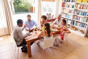 amici seduti a un tavolo a parlare durante una cena