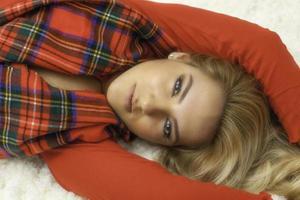 bella ragazza bionda in abito rosso e sciarpa natalizia foto
