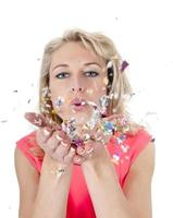 giovane donna che soffia coriandoli foto