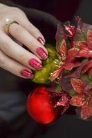 mano della moglie con le unghie dipinte che tengono l'ornamento di natale.
