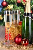 bottiglia di champagne con bicchieri su sfondo albero di natale foto