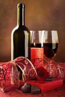vino rosso, candele e cuori di cioccolato, natura morta foto