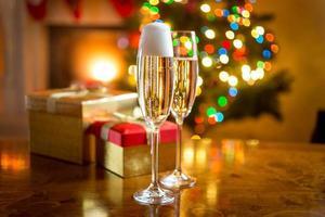 due bicchieri di champagne contro il camino decorato per Natale