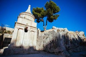 antica tomba scolpita nella pietra con sopra un albero verde