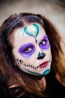 giovane donna con il trucco del cranio dello zucchero