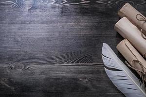 antichi rotoli di carta piuma su copyspace tavola di legno foto