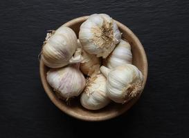 teste d'aglio in una ciotola di legno foto