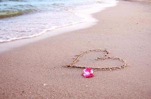 cuore nella sabbia in riva al mare foto
