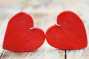 due cuori di legno rossi sulla superficie in legno foto