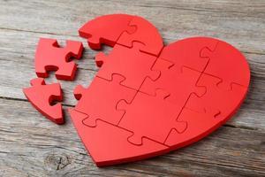 cuore rosso puzzle su fondo di legno grigio foto