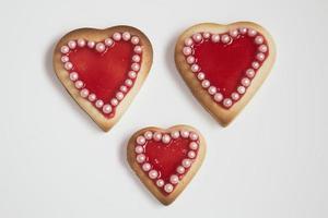 tre romantici biscotti di San Valentino fatti in casa a forma di cuore su un wh foto