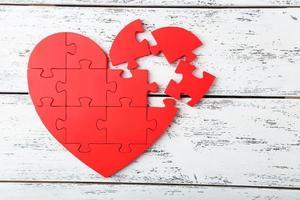 cuore puzzle rosso su fondo di legno bianco foto