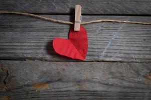 cuore rosso appeso al bucato. sullo sfondo di legno vecchio.