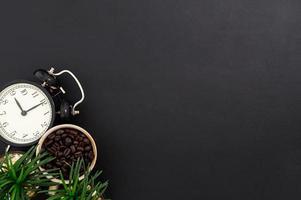 tazza con chicchi di caffè e un orologio sulla scrivania