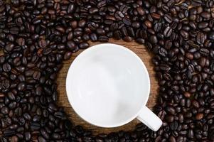 tazza vuota posta sul tavolo con chicchi di caffè intorno foto