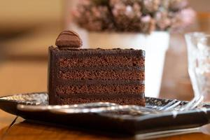 Close up di torta al cioccolato a fette sulla scrivania in legno foto