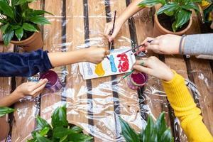 bambini che immergono i pennelli nella vernice foto