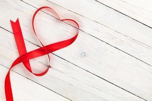 nastro a forma di cuore di San Valentino su un tavolo di legno bianco foto